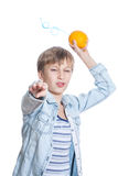 Beautiful funny child in stylish shirt throws a orange grenade Stock Photo