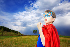 Beautiful funny child superhero wearing a cape standing in a green summer field. Beautiful child superhero wearing a cape standing in a green summer field with stock photography