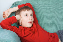 Beautiful funny child wearing bright red sweater resting on a sofa dreaming. Beautiful funny child wearing bright red sweater resting on a sofa smiling and Stock Photography