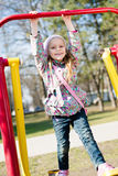 Beautiful funny cute little girl having fun riding a swing looking at camera & happy smiling in the park on spring or autumn Stock Photography