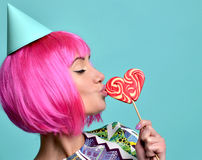 Beautiful funny fashion cheerful woman in hot pink party wig eat Royalty Free Stock Image