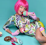 Beautiful funny fashion cheerful woman in hot pink party wig eat Stock Photography