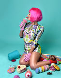 Beautiful funny fashion cheerful woman in hot pink party wig eat Royalty Free Stock Photography