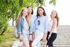 Beautiful funny four girlfriends rejoice and smile at the camera in the Park in the summer stock image