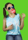 Beautiful funny girl wearing sunglasses with bubble of chewing gum listens to the music Royalty Free Stock Image