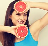 Beautiful funny grimacing brunette woman holding fresh red grapefruit near the face and looking humor on blue background stock photography