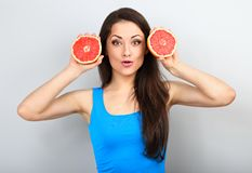 Beautiful funny grimacing brunette woman holding fresh red grapefruit near the face and looking humor on blue background royalty free stock photography