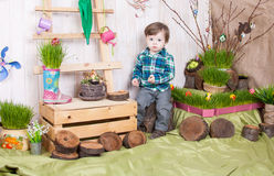Beautiful funny little boy playing among easter spring scenery. Studio filming a child in a bright, juicy spring location. Child is happy and cheerful royalty free stock images