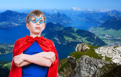 Beautiful funny little child superhero standing on top of a big mountain Stock Images