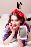 Beautiful funny sexy pinup girl relaxing lying in bed showing mobile phone display happy smiling & looking at camera Royalty Free Stock Photos