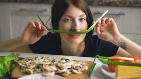 Beautiful funny woman cook play with green onion on table in kitchen at home. Indoors Royalty Free Stock Photos