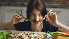 Beautiful funny woman cook play with green onion on table in kitchen at home. Indoors Stock Photo