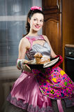 Beautiful funny young pinup woman in a dress and apron happy smiling and baking yummy cake portrait Royalty Free Stock Photo