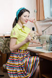 Beautiful funny young pinup woman with sewing machine Stock Photo