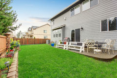 Beautiful furnished back yard with patio and fence. Stock Photography