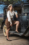 Beautiful Gangster Pin-Up. Beautiful armed gangster woman with leg up on car Royalty Free Stock Images