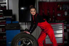 Beautiful Garage Girl. A beautiful brunette female mechanic pushing a tire in a garage Stock Photo
