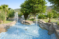 Beautiful garden with azure fountain Royalty Free Stock Image