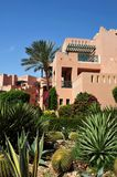 Beautiful garden at hotel resort and building in traditional arabic style. Resort architecture in Egypt.  Royalty Free Stock Photos