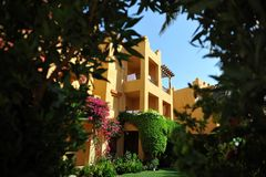 Beautiful garden at hotel resort and building in traditional arabic style. Resort architecture in Egypt.  Royalty Free Stock Photography