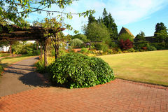 Beautiful garden in the park. With wooden pergola Stock Photos