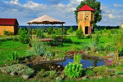 Beautiful garden during a summer day. Beautiful garden with arbor, pond and old tower against vivid summer sky Royalty Free Stock Photography