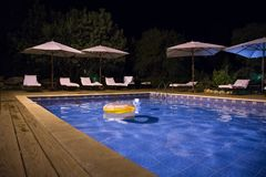 Beautiful garden with swimming pool and loungers. Night calm scene stock photos