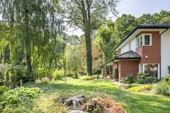 Beautiful garden with trees and shrubs. Next to a big house. Real photo royalty free stock image