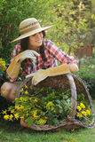 Beautiful gardener posing with wicker basket full of flower Stock Images