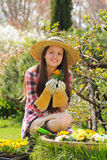 Beautiful gardener smiles with flower in hand Stock Photography
