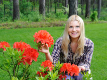 Beautiful gardener woman with red flower Stock Photos