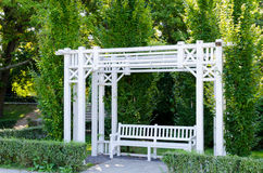 A beautiful gazebo and a bench painted in white in a park.  Stock Image