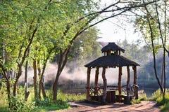 Beautiful gazebo among trees and lake. Beautiful wooden gazebo among trees and lake on sunny summer day Stock Image