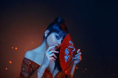 A beautiful geisha with blue long hair and a bang is looking in soul. red make up, lips, long dress with open shoders. And deep neckline. holding scarlet fan in royalty free stock images
