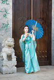 Beautiful geisha with a blue umbrella Royalty Free Stock Images