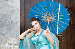 Beautiful geisha with a blue umbrella Royalty Free Stock Photos