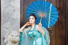 Beautiful geisha with a blue umbrella Stock Photos