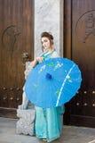 Beautiful geisha with a blue umbrella Royalty Free Stock Photos