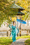 Beautiful geisha with a blue umbrella near green apple tree Royalty Free Stock Image
