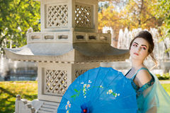 Beautiful geisha with a blue umbrella Royalty Free Stock Photo