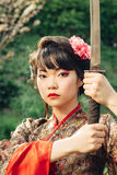 Beautiful geisha in kimono with samurai sword Stock Images