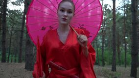 A beautiful geisha in a red kimono looking at the camera and walking in a coniferous forest, slow motion