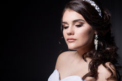 Beautiful gentle girl portraits of the bride in a white wedding dress with evening hairstyle with a rim of flowers in her hair and Royalty Free Stock Image