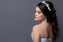 Beautiful gentle girl portraits of the bride in a white wedding dress with evening hairstyle with a rim of flowers in her hair and. Make-up in studio Stock Photos