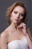 Beautiful gentle girl portraits of the bride in a white wedding dress with evening hairstyle with a rim of flowers in her hair and Stock Images