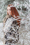 Beautiful gentle girl with red hair in a fur vest standing in a snowy forest with iniem on the branches of trees Royalty Free Stock Photography