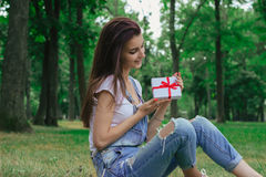 Beautiful gentle girl sits on the grass and holding a gift Stock Photos