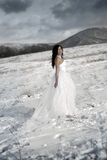 The beautiful gentle girl in white dress. Dances on snow Royalty Free Stock Photos