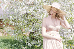 Beautiful gentle lovely girl in a summer hat with a light make-up, with full lips walks in blooming garden on a bright warm day so Royalty Free Stock Images
