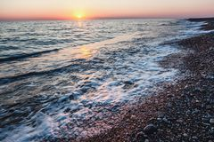 Beautiful gentle sunset at the sea, bright sun and pebble beach Royalty Free Stock Image
